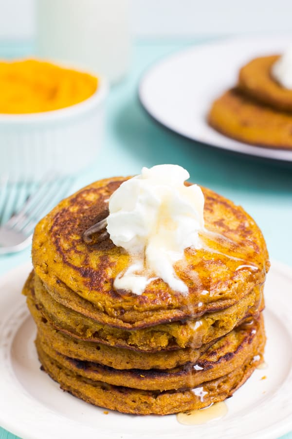 A pile of gluten free pumpkin pancakes on a white plate.