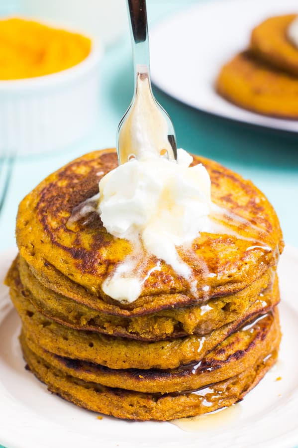 Fork sticking in to stack of gluten free pumpkin pancakes.