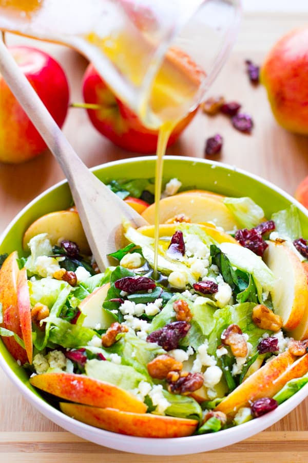 Dressing being poured onto apple and blue cheese salad in green bowl.