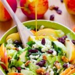 Apple, candied walnuts and Blue Cheese Salad in a white bowl with dressing.