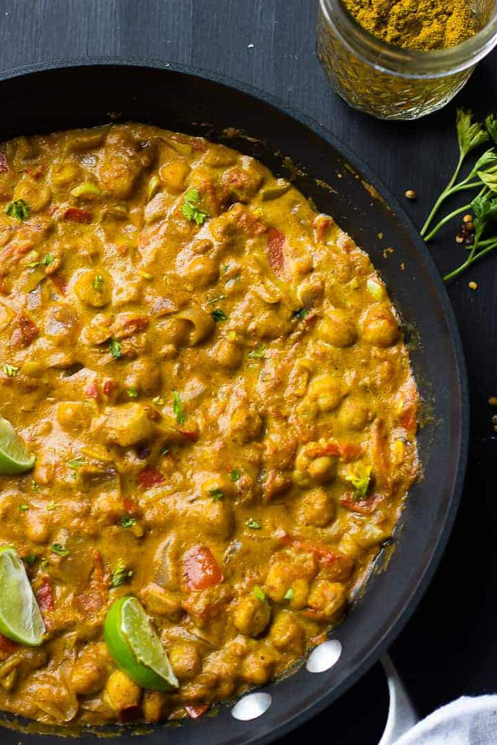 coconut chickpea curry in a pot with lime slices on top in a closeup shot