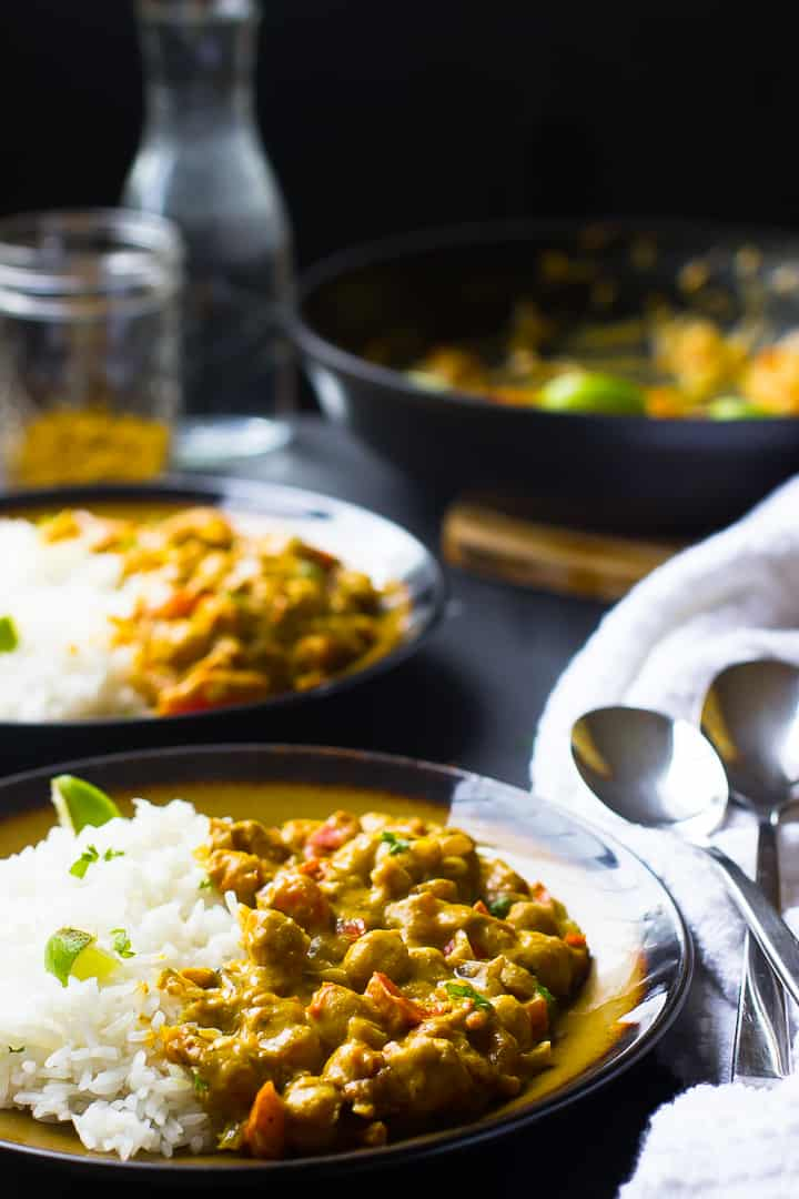coconut chickpea curry in two plates side angle view with rice and lime slices with the pot in the background