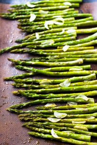 Top down shot of garlic roasted asparagus on a baking sheet.