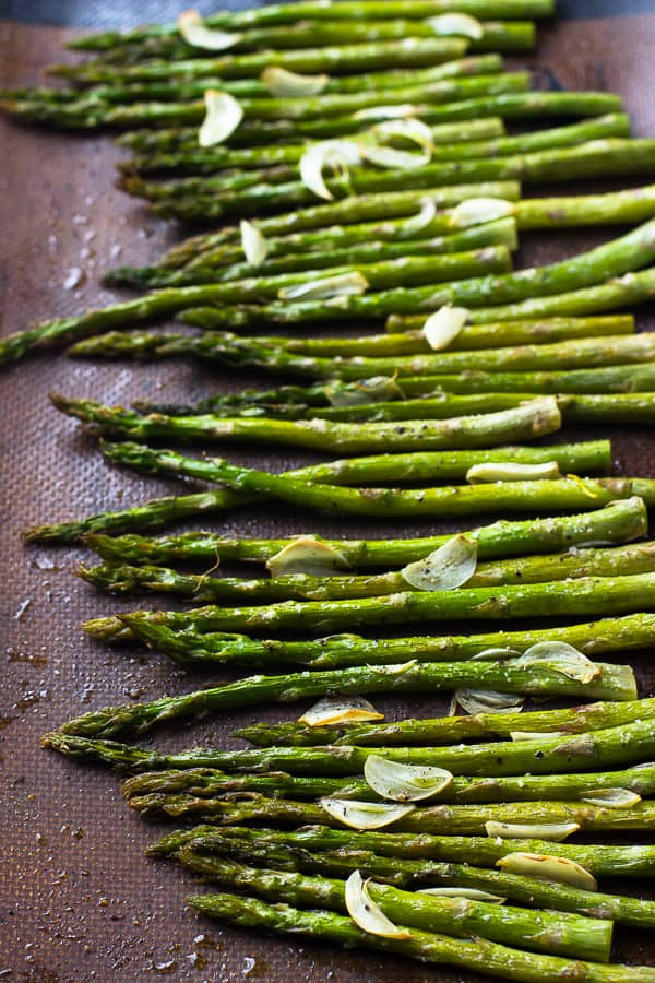 Top down shot of garlic roasted asparagus on a baking tray.