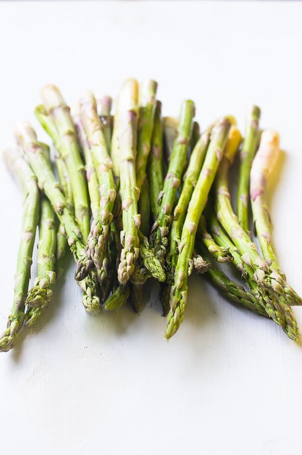 A bunch of raw asparagus on a white table top.