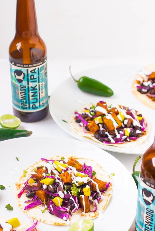 Black bean and sweet potato tacos on white plates with two bottles of beer.