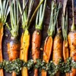 A row of roasted carrots on a baking sheet.