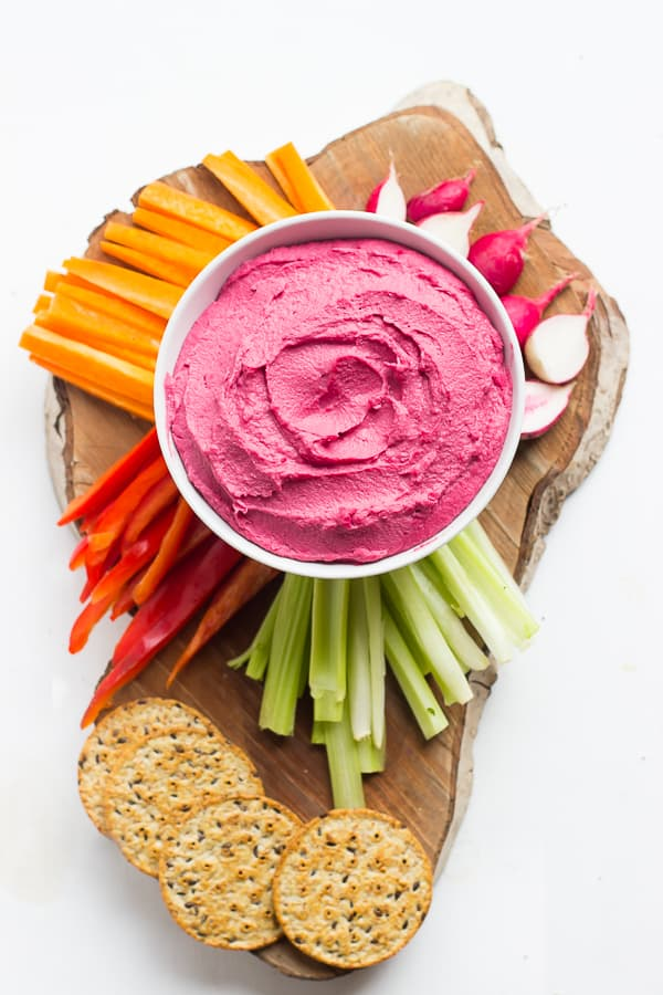 Overhead shot of beet hummus in a white bowl surrounded by crackers and raw vegetables.