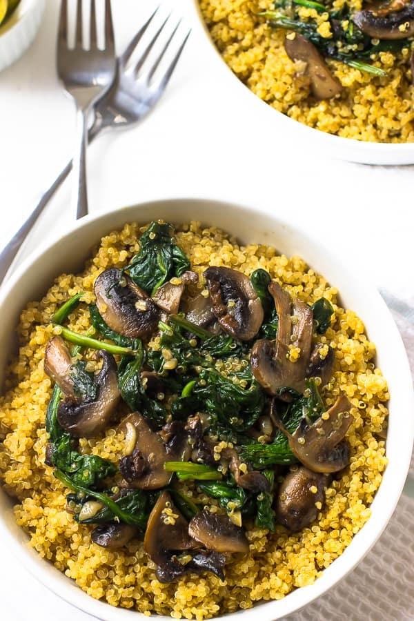 Overhead shot of creamy coconut spinach and mushroom quinoa in a white bowl.