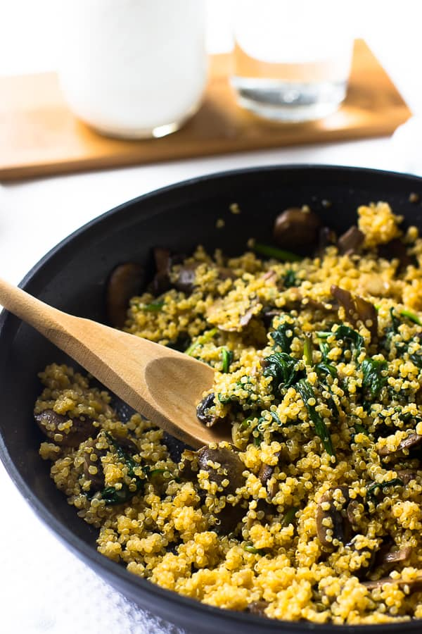 Creamy coconut spinach and mushroom quinoa with a wooden spoon in a black skillet.