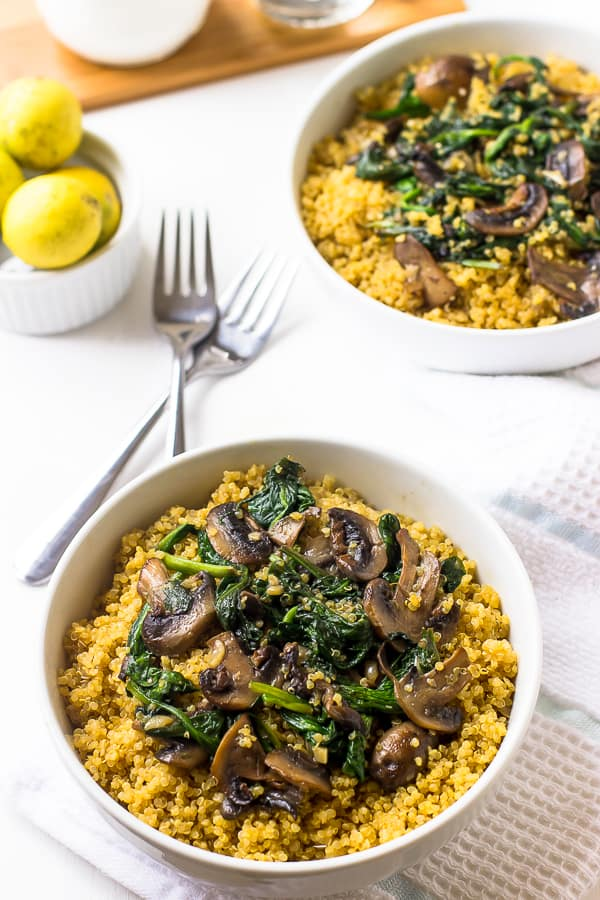 Two bowls of creamy coconut spinach and mushroom quinoa.
