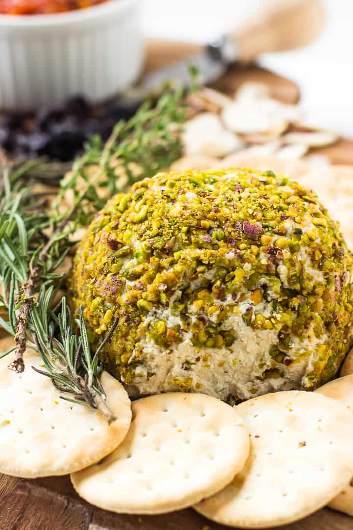 A pistachio crusted vegan cheese ball with crackers on the side.