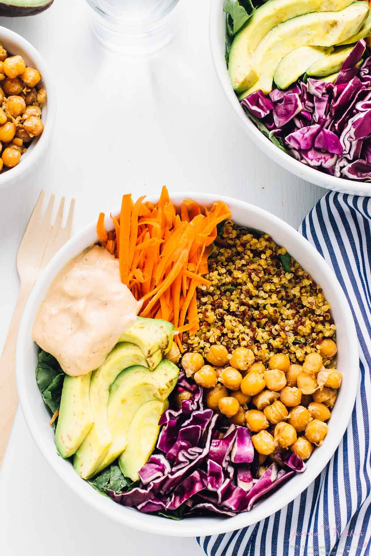 Top down shot of nourish Buddha Bowl on a white table with a wood fork on the side.