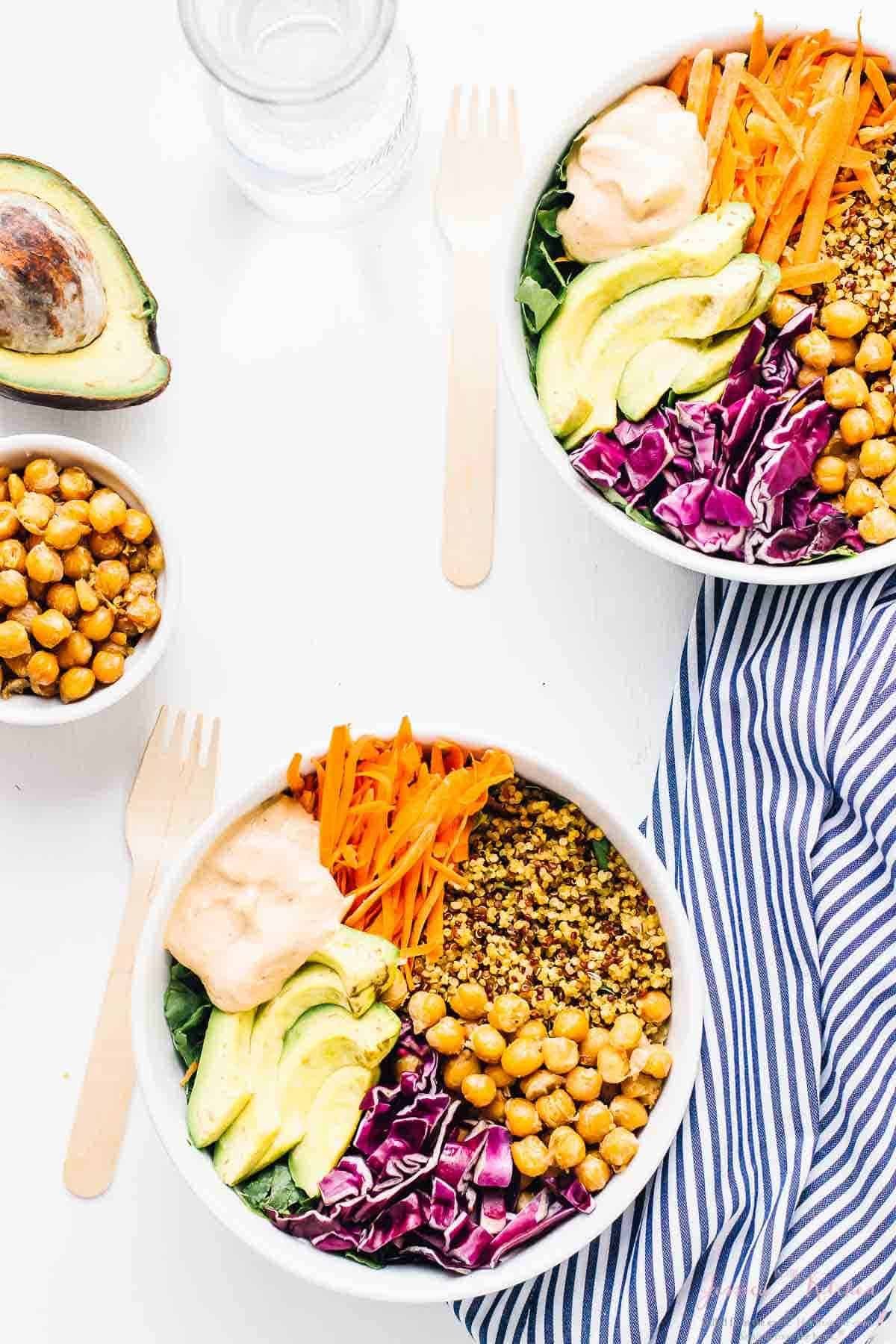 Overhead shot of two nourish buddha bowls on a white table.