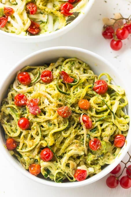 Pesto zucchini noodles in a white bowl.