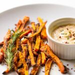 Baked carrot fries on a white plate with tahini dip on the side.