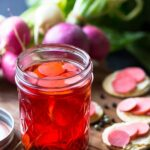 Pickle radishes in a glass jar on a board with radishes in the background.