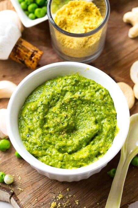 Cashew pea pesto in a white ramekin with a poon on the side.