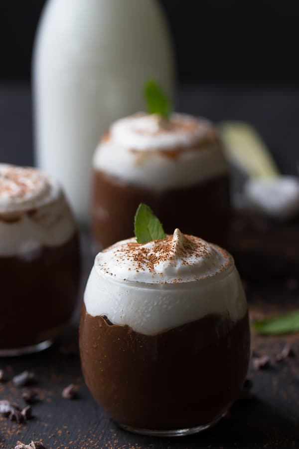 Side shot of three chocolate avocado puddings in glasses.