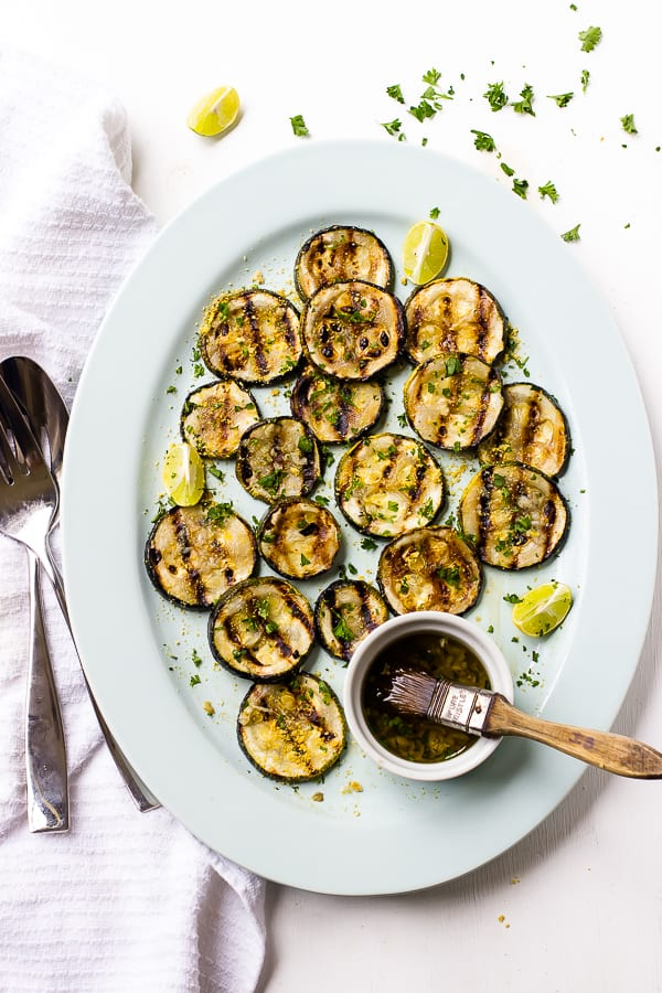 Top down shot of lemon garlic grilled zucchini on a long white plate.