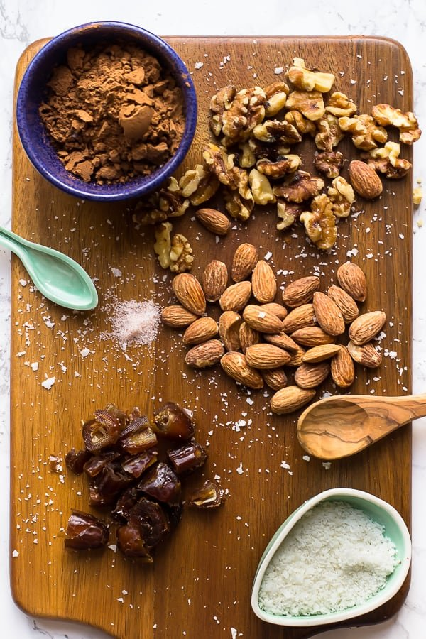 ingredients to make no bake brownie energy bites on a cutting board ( almonds coconut flakes, dates, coco powder, salt and walnuts)