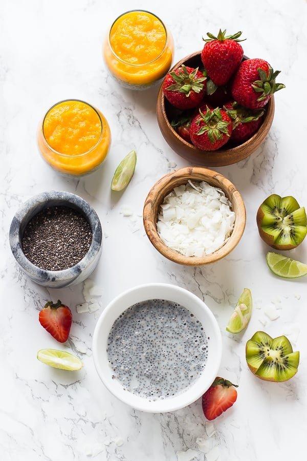 Top down shot of ingredients for mango coconut chia pudding on a white table top.