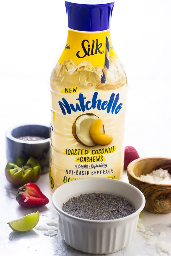A bottle of nutchello nut milk on a table with chia seeds in ramekin.