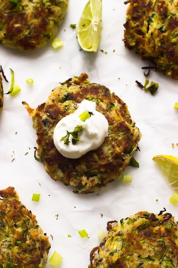 A vegan zucchini fritter with sauce on top.
