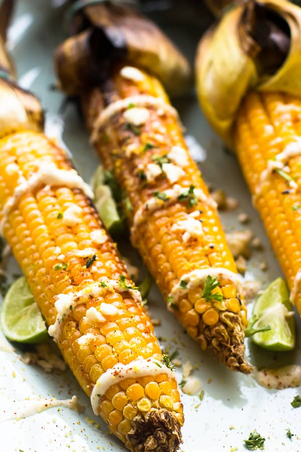 This Grilled Mexican Street Corn is grilled to smoky perfection then smothered in a delicious and creamy vegan mayonnaise blend and Lime Crema. It's the best side dish! | https://jessicainthekitchen.com