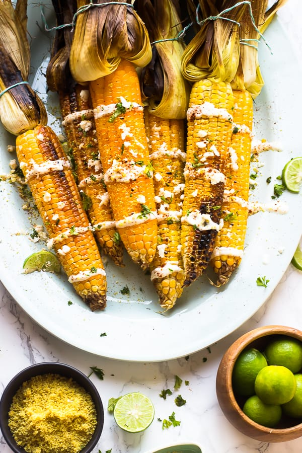 Overhead shot of grilled mexican street corn on a white dish with a bowl of limes.