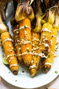 Top down shot of grilled corn on a white plate.