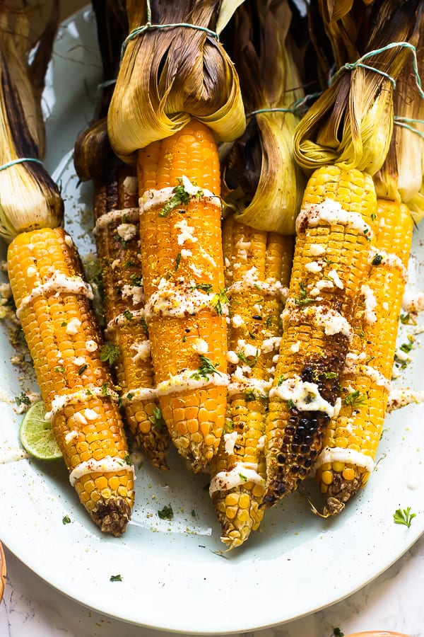 This Grilled Mexican Street Corn is grilled to smoky perfection then smothered in a delicous and creamy Lime Crema. It's the best side dish!