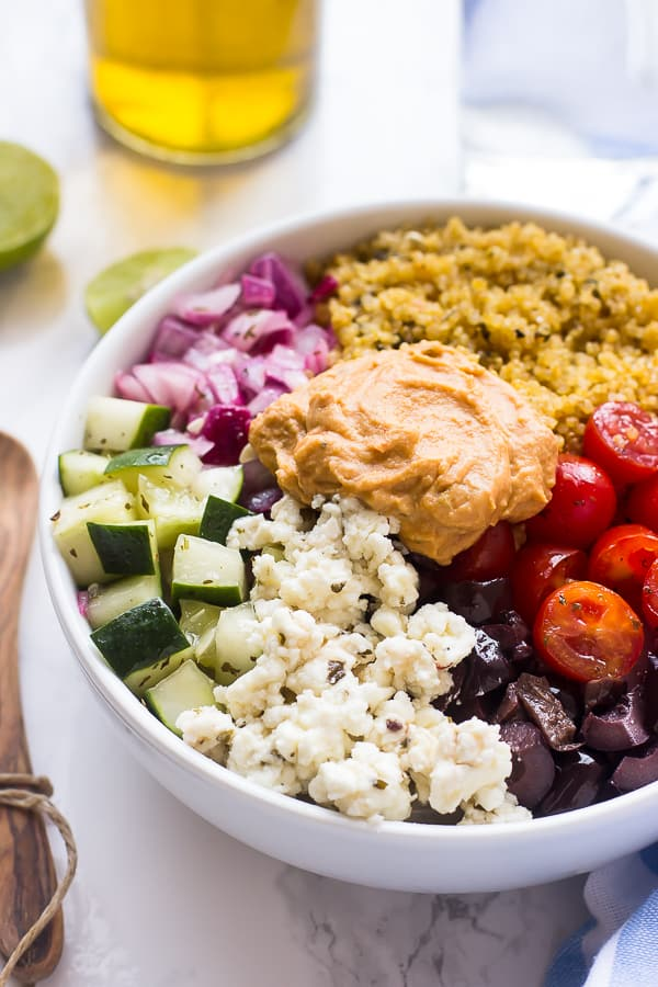 Mediterranean quinoa salad bowl on a table with a wood spoon.