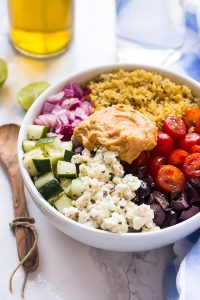 Mediterranean salad in a white bowl on a table.