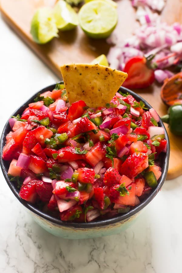 Strawberry jalapeno salsa in a bowl with a chip dipped in.