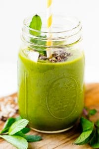 Mint chocolate chip green smoothie in a mason jar with a straw and sprig of mint.