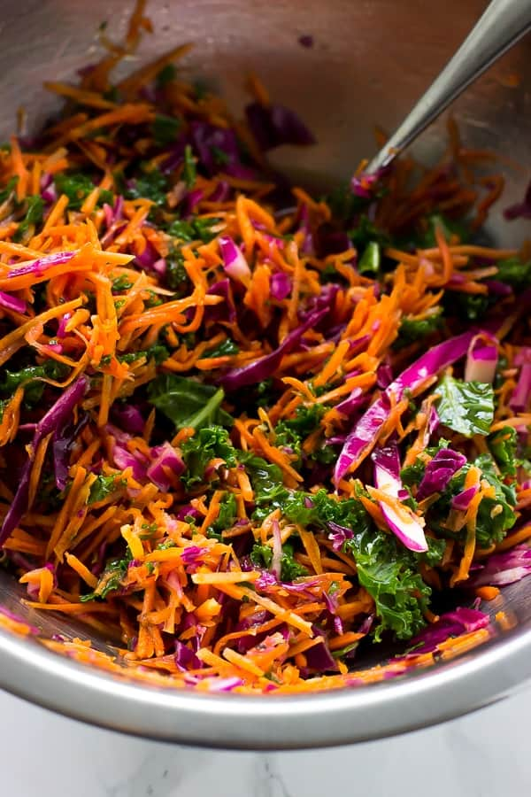 Mixing a bowl of shredded cabbage and carrot.