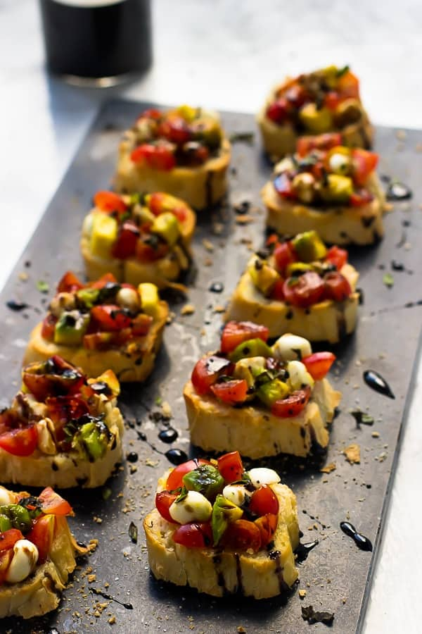Rows of bruschetta drizzled with a balsamic reduction on a grey slate.
