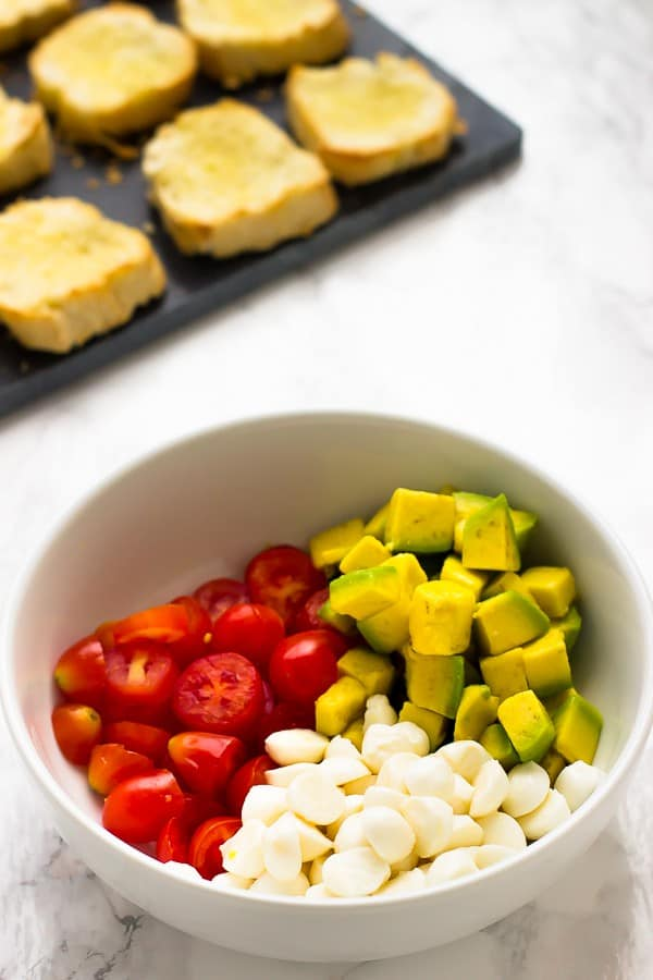 A white bowl containing diced avocado garlic and tomatoes.
