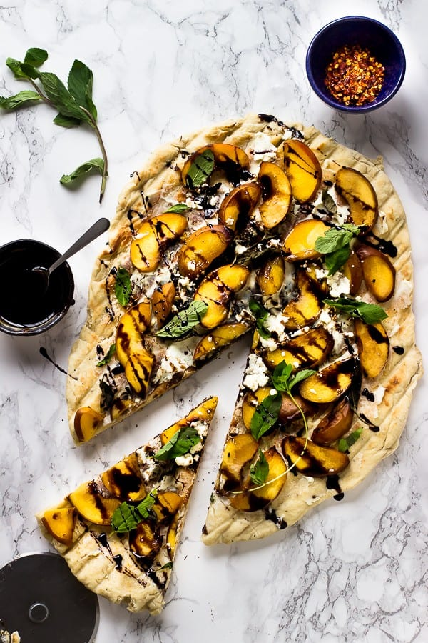 Top down shot of grilled peach pizza with a slice cut out.