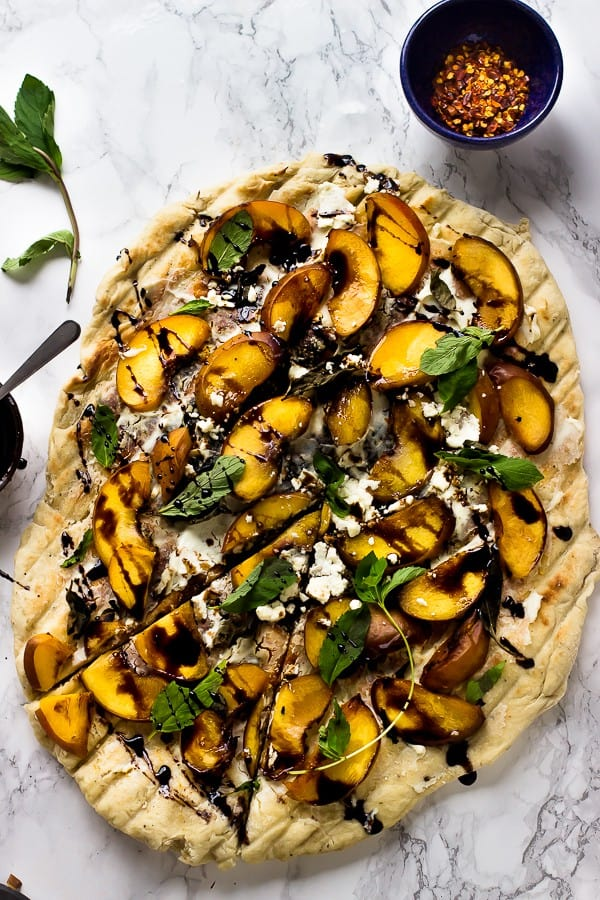 Overhead shot of grilled peach, basil and goat cheese pizza on a marble counter with a bowl of chili flakes on the side.