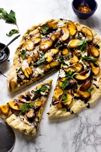 Top down shot of grilled peach pizza on a marble counter.