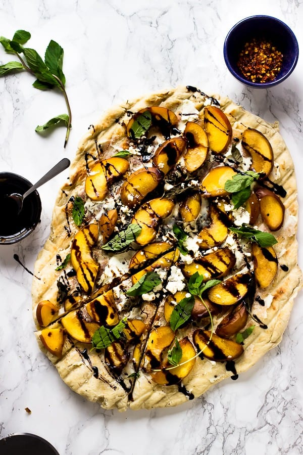 Overhead shot of grilled peach, basil and goat cheese pizza on a marble tabletop.