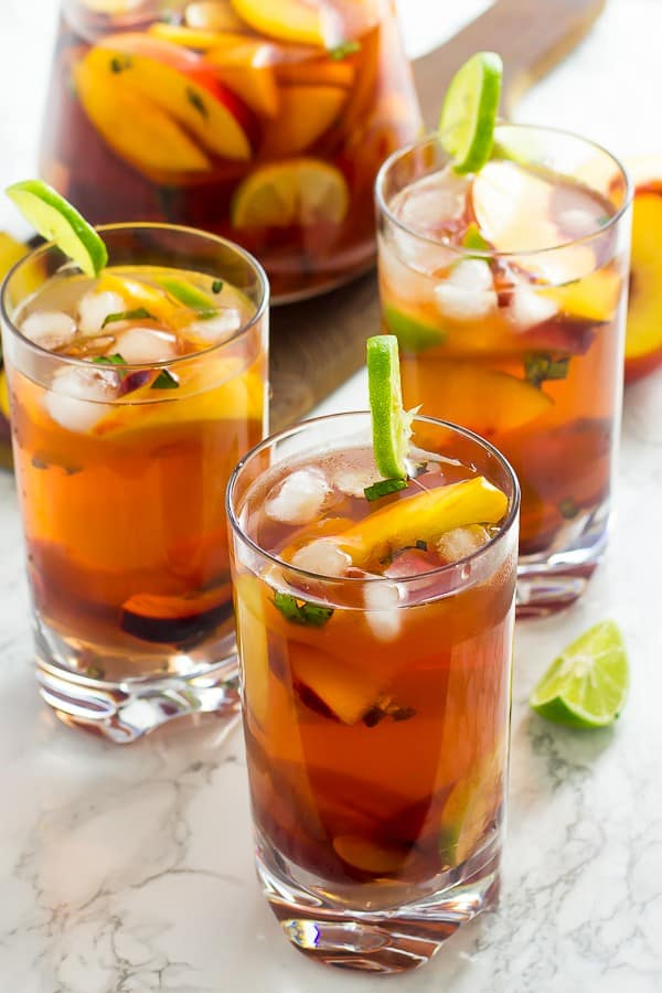 Three glasses of stone fruit sangria with slices of lime.