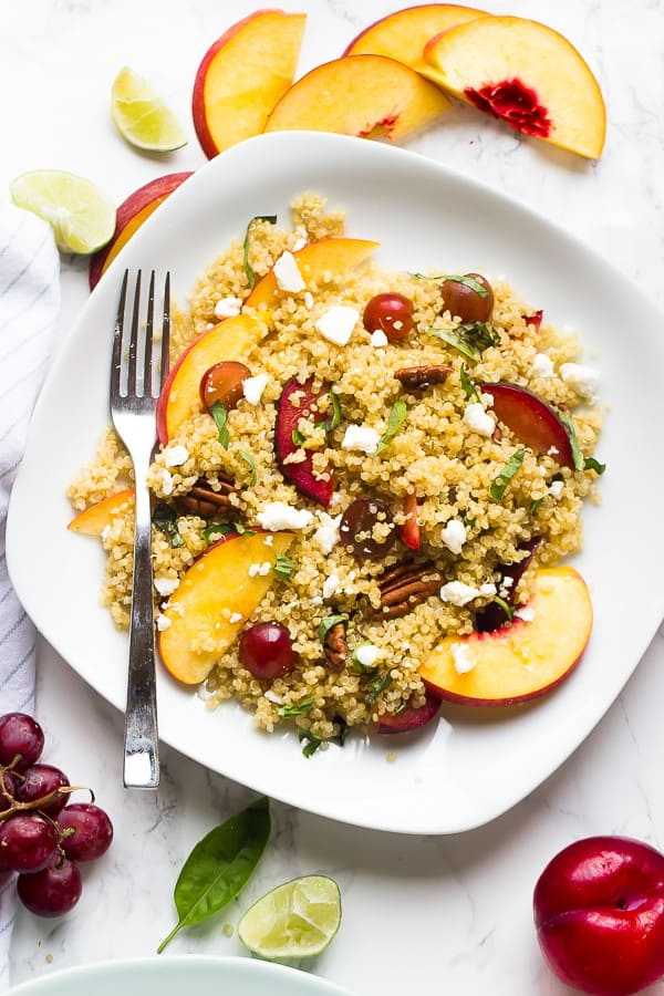 Overhead shot of quinoa stone fruit salad on a square white plate with a fork on the side.