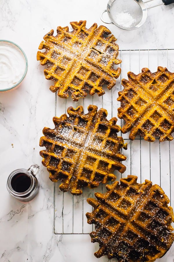 Four flourless vegan pumpkin waffles on a wire rack.
