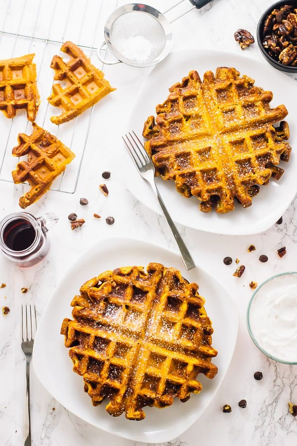 Overhead shot of vegan pumpkin waffles on square white plates with forks on the side.