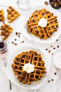 Top down shot of two flourless vegan pumpkin spice waffles on square white plates.