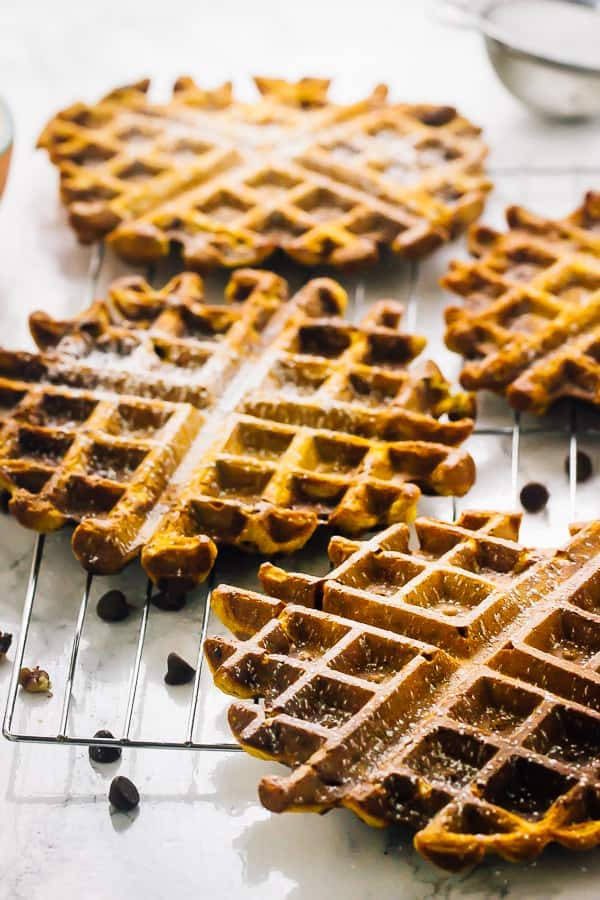 Side shot of flourless vegan pumpkin waffles on a wire rack.