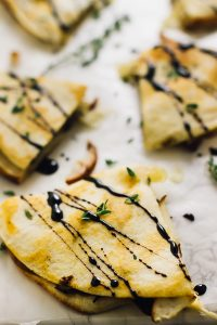 Overhead shot of pear brie & caramelised onions quesadillas on parchment paper.